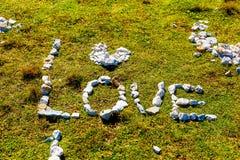 Fassen Sie die Liebe ab, die von den Kieselsteinen auf Bergwiese gemacht wird Lizenzfreie Stockfotografie