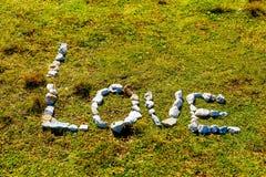Fassen Sie die Liebe ab, die von den Kieselsteinen auf Bergwiese gemacht wird Stockbild