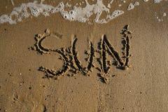 Fassen Sie die Sonne ab, die auf den Sand geschrieben wird, der durch Wellen gewaschen wird Stockfotos