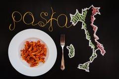 Fassen Sie die Teigwaren ab, die von gekochten Spaghettis gemacht werden und die trockenen Teigwaren auf dem schwarzen Hintergrun Stockbild