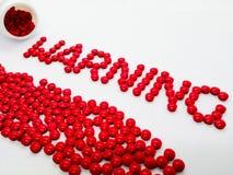 Fassen Sie die Warnung ab, die von den roten Tabletten gemacht wird, lokalisiert auf weißem Hintergrund lizenzfreie stockfotografie