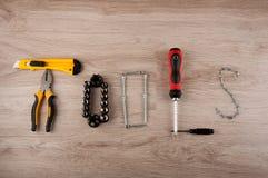 Fassen Sie die Werkzeuge ab, die durch die Reparaturausrüstung hergestellt werden, die auf Holztisch legt lizenzfreie stockfotos