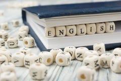 Fassen Sie Englisch ab, das mit hölzernen Buchstaben des Blockes nahe bei einem Stapel anderen Buchstaben über Holztisch gemacht  Stockfotografie