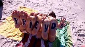 Fassen Sie Freunde auf den Füßen jungen Frauen ab, die am Strand liegen