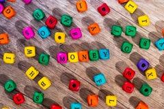 Fassen Sie ` Geld ` der farbigen hölzernen Würfel ab Stockfotografie