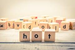 Fassen Sie ` heißes ` hölzernes Kubik auf dem Holz ab Lizenzfreies Stockfoto