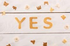 Fassen Sie ja von den Frühstückskost- aus Getreidebuchstaben und von den AlphabetCorn Flakes auf Holztisch ab Lizenzfreie Stockfotografie