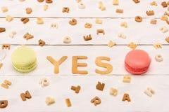 Fassen Sie ja von den Frühstückskost- aus Getreidebuchstaben und von den AlphabetCorn Flakes mit macarons auf Holztisch ab Lizenzfreie Stockbilder