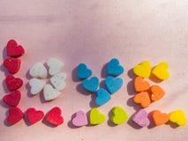 Fassen Sie Liebe mit den mehrfarbigen Herzen ab, die auf rosa Hintergrund geformt werden Stockbild