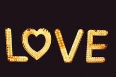 Fassen Sie Liebe von den großen Buchstaben mit glühenden Glühlampen auf einer Dunkelheit ab Lizenzfreie Stockfotos