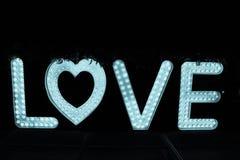 Fassen Sie Liebe von den großen Buchstaben mit glühenden Glühlampen auf einer Dunkelheit ab Stockfoto