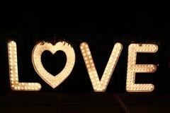 Fassen Sie Liebe von den großen Buchstaben mit glühenden Glühlampen auf einer Dunkelheit ab Stockfotografie