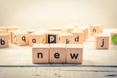 Fassen Sie ` neues ` hölzernes Kubik auf dem Holz ab Lizenzfreie Stockfotografie