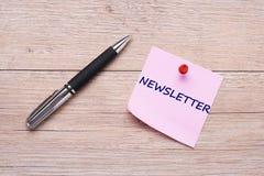 Fassen Sie Newsletter auf rosa klebriger Anmerkung mit rotem Stift ab Lizenzfreie Stockfotos