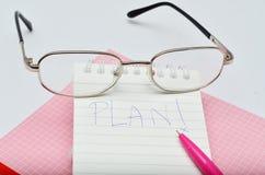 Fassen Sie Plan messege auf rosa Stiftnotizbuch mit Gläsern ab stockfotos