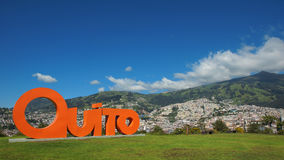 Fassen Sie QUITO ab, das mit orange Buchstaben in 3 Maßen mit der Stadt von Quito im Hintergrund gemacht wird Lizenzfreies Stockfoto