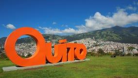 Fassen Sie QUITO ab, das mit orange Buchstaben in 3 Maßen mit der Stadt von Quito im Hintergrund gemacht wird Lizenzfreie Stockfotos
