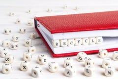 Fassen Sie Recycle geschrieben in Holzklötze im roten Notizbuch auf weißes w ab stockfotos