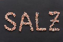 Fassen Sie Salz ab, das in rosa Hymalayan-Salzkristalle geschrieben wird Lizenzfreie Stockfotografie