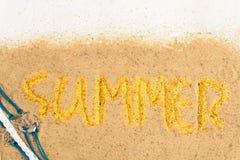 Fassen Sie ` Sommer ` Schreiben auf Sand mit Oberteilen über weißer hölzerner Rückseite ab Lizenzfreie Stockfotos