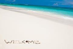 Fassen Sie Willkommen auf einem weißen Sandstrand nahe blauem Ozean ab Stockfotos