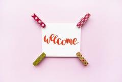 Fassen Sie willkommenes handgeschriebenes mit Aquarell in der Kalligraphieart, Miniaturwäscheklammern auf einem rosa Hintergrund  Lizenzfreie Stockfotos