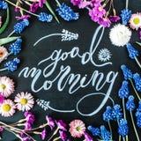 Fasst den guten Morgen ab, der mit Kreide in Kalligraphieart auf schwarze Tafel geschrieben wird Stockfotografie