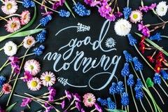 Fasst den guten Morgen ab, der mit Kreide in Kalligraphieart auf schwarze Tafel geschrieben wird Stockbilder