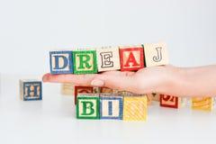 """Fasst """"dream big† ab, das mit hölzernen Buchstabewürfeln buchstabiert wird Stockfotografie"""
