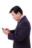 Fassungsloser, entsetzter Geschäftsmann, der schlechte Nachrichten über Smartphone empfängt Stockfotografie
