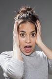 Fassungsloses junges multiethnisches Mädchen, das erschrocken schaut Stockbild