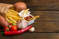 Fastów food produkty: francuzów dłoniaki z kumberlandem i karmowymi składnikami na ciemnym drewnianym stole z kopii przestrzenią, fotografia stock