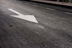 Fast arrow. Traffic sign of obligation printed in the asphalted road. Motion blur is deliberated. The focus is in the arrow Stock Photo