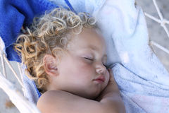Fast asleep. A caucasian child fast asleep on a hammock with her hand placed under one cheek Stock Photography