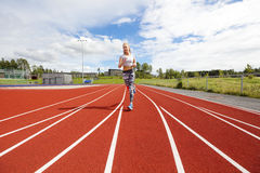 Fast athletic female runner on outdoor running track. Female athlete runner or sprinter on running track. Workout outdoor Royalty Free Stock Images