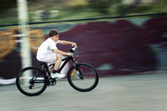 Fast bike ride. 11 years old boy caught in motion while riding a bicycle very fast Stock Images
