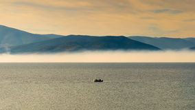Fast boat travelling against the dramatic sky and the morning fog as background. Stock Photos