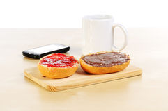 Fast breakfast with bread roll cup of coffee and mobile phone Stock Photo