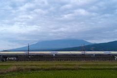 Fast bullet train driving and passing Mountain Fuji near Tokyo r royalty free stock photography