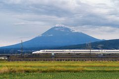 Fast bullet train, driving and passing Mountain Fuji near Tokyo. Railway station with green rice field, Japan stock photo