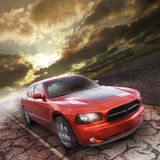 Fast car. A rust colored sporty car speeds down an old road in a deserted dry area with a dramatic sunrise or sunset cloudy sky.  This is a dodge charger with a Stock Photos