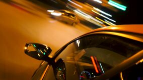 Fast car driving through night city. Stock footage. Timelapse of driving car around city with lights at night. Close-up
