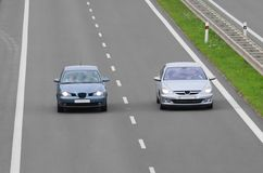 Fast car on a highway. Overtaking another one Royalty Free Stock Photos