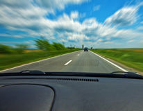 Fast car on road viewed from the interior Royalty Free Stock Images