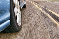 Fast Car Wheel Speeding on a Country Road. Fast car speeding and cornering on a country road with wheel detail and road motion blur Stock Photos