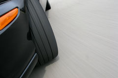 Fast Car Wheel Tire Speeding and Cornering on Road. Fast car turning wheel tire detail speeding and cornering on road with real pavement speed motion blur Royalty Free Stock Photos
