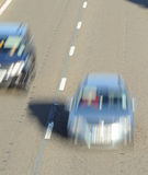 Fast cars driving on motorway. High angle view of two cars driving on motorway with motion blur effect royalty free stock photos