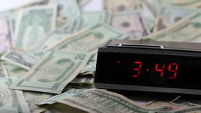 Fast Clock with Still Money. A red numbered digital clock with a browse button moves the time display rapidly while a variety of American dollars lays on a white stock video footage