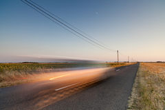 Fast communication. Straight road ending on horizon with electric wires alongside. Blurred car in foreground going forward imitating speed and fast communication Stock Photos