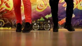 Fast dancing legs of two boys. A breakdance steps on the background of graffiti and a cool boobox stock video footage